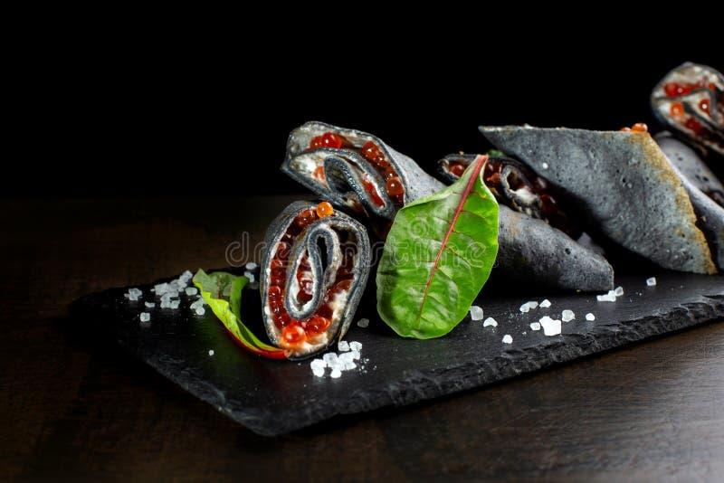 Svarta pannkakor som stoppas med kaviaren för röd lax fotografering för bildbyråer