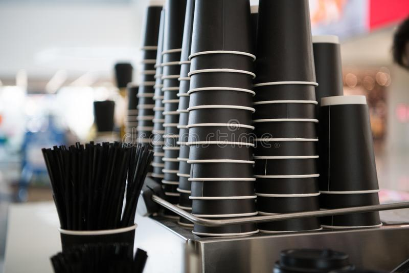 Svarta pappers- koppar på en räknare mot bakgrunden av en suddig cafeteria på gallerian med takeaway kaffe som går arkivfoto