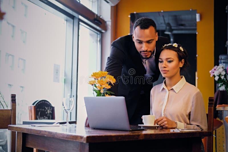 Svarta par genom att använda bärbara datorn i ett kafé royaltyfri bild