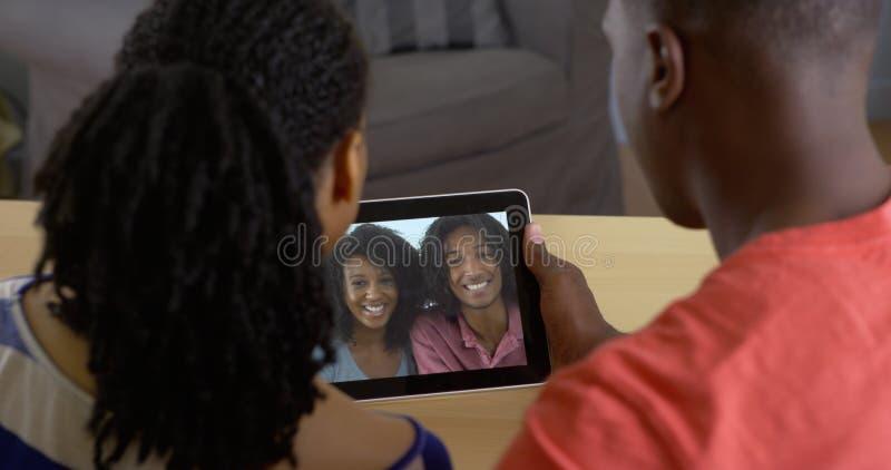Svarta par som talar till vänner över video pratstund för minnestavladator royaltyfria bilder