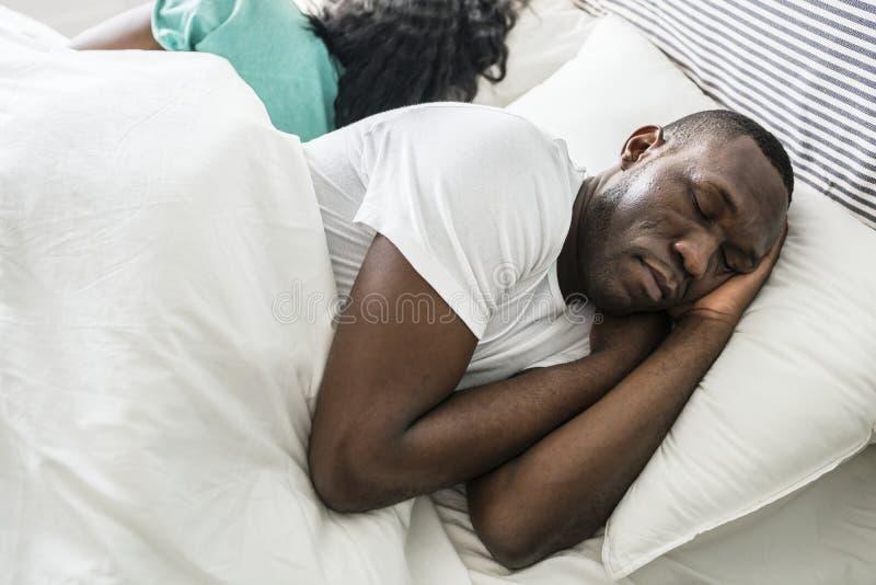 Svarta par som tillsammans sover i säng royaltyfria bilder