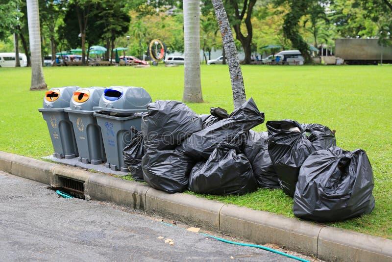 Svarta plast- avfallpåsar på trädgård för grönt gräs nära gatan arkivfoto