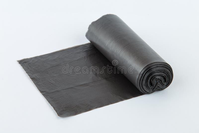 Svarta plast- polyetylenavskrädepåsar rullar isolerat över den vita bakgrunden arkivbild