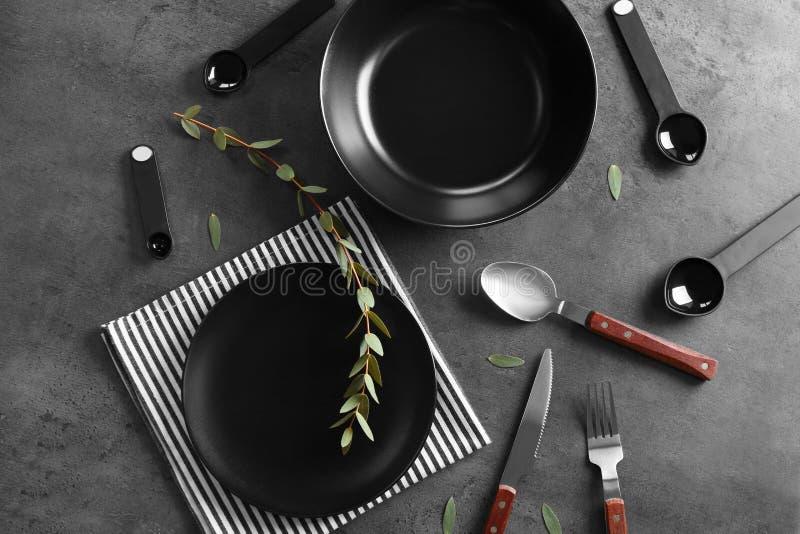 Svarta plattor och bestick på grå bakgrund fotografering för bildbyråer