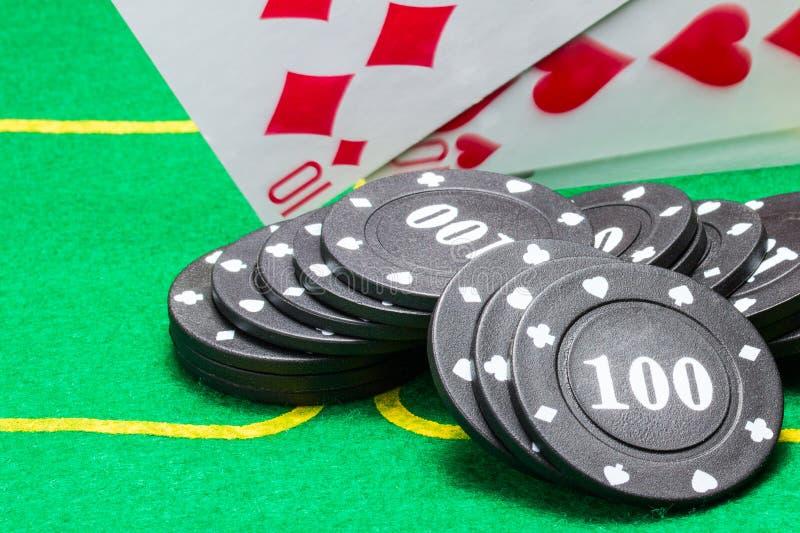 Svarta pokerchiper ligger på den gröna kanfasen mot bakgrunden av fallande spela kort royaltyfri bild