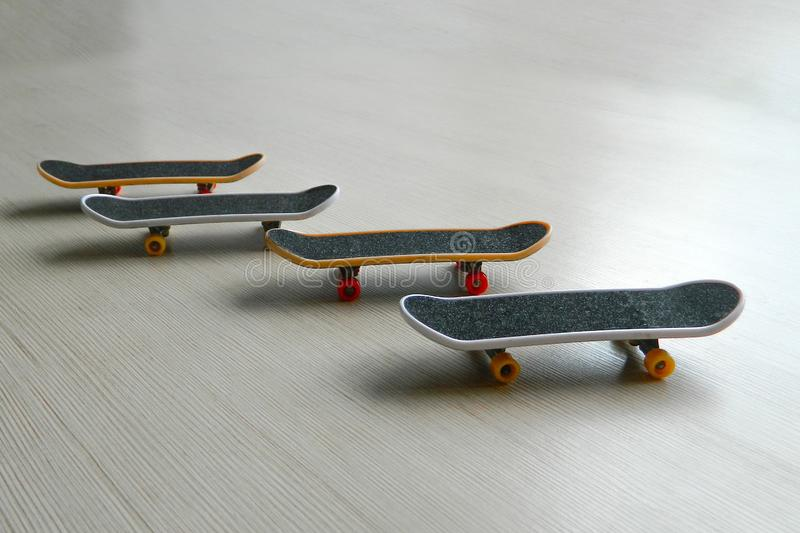 Svarta skateboarder på grå randig yttersida Skridskobrädegrupp av fyra med skuggor och den delvis mjuka fokusen Perspektivsikt av arkivfoton