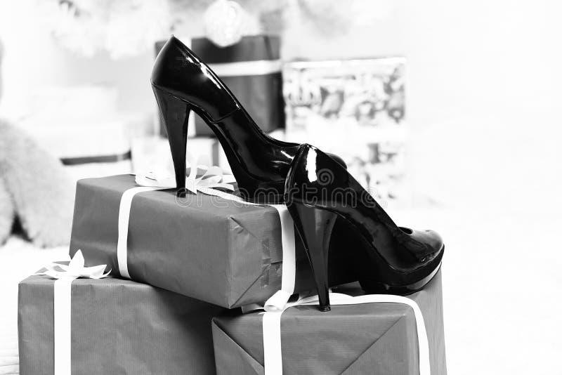 Svarta skor för patenterat läder som står på stora blåa julgåvor eller gåvor på vit studiobakgrund, selektiv focu royaltyfri fotografi