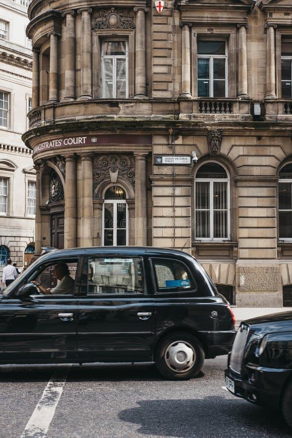Svarta taxiar framme av en byggnad på gatan för drottning Victoria i stad av London, UK royaltyfri foto