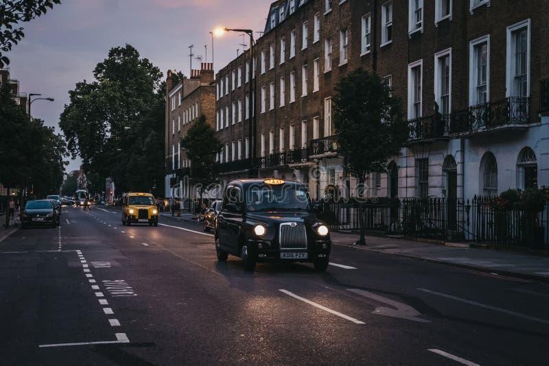Svarta taxiar med den upplysta taxien undertecknar på en gata i London, UK royaltyfria bilder