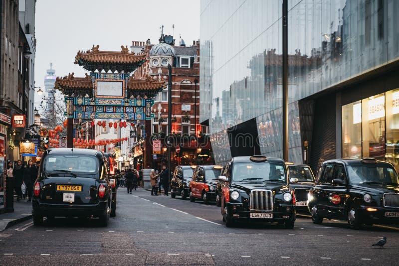 Svarta taxiar som framme parkeras på taxirangerna av ingången till den Kina staden, Piccadilly Circus, London, UK fotografering för bildbyråer