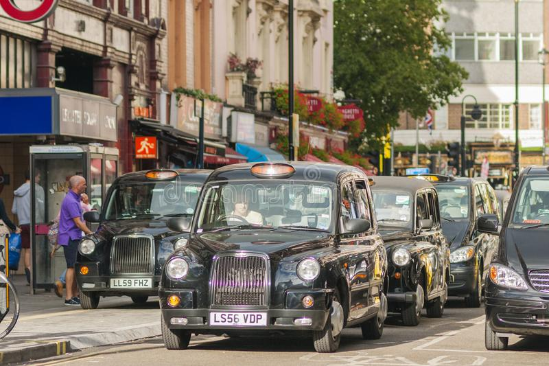Svarta taxiar som väntar på grön segnal på en trafikljus nära Leic arkivfoto