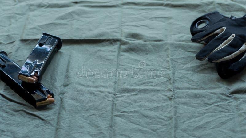 Svarta tidskrifter för stålhandeldvapenpistol som laddas med ihåliga punktammunitionar och svarta och solbrända taktiska handskar arkivbild