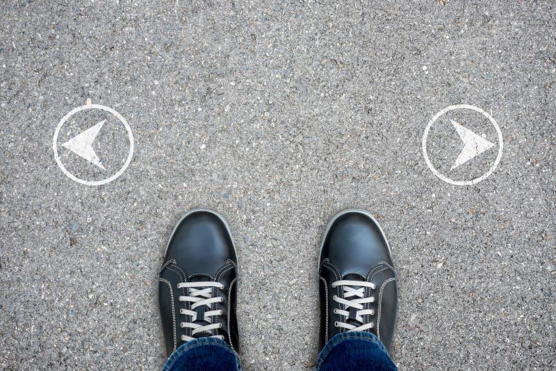 Svarta tillfälliga skor som står på den arga vägen royaltyfri bild