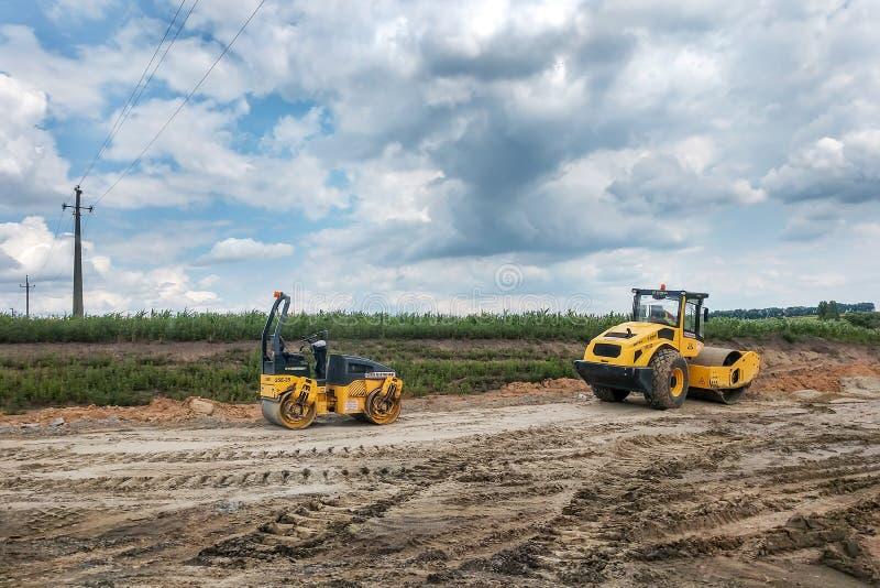 Svarta två och gula vägasfaltrullar står på jordningen som göras strimmig med spår från gummihjulen av arbetande maskiner arkivfoto