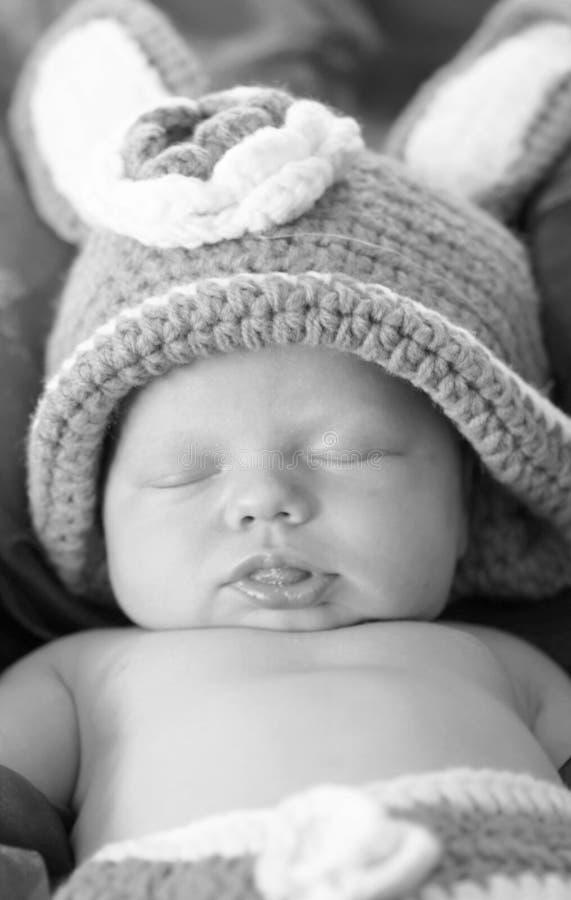 Svarta vita den nyfödda ståendenärbilden behandla som ett barn att sova i kanindräkt royaltyfri foto