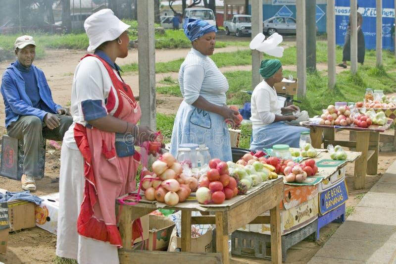 Svarta zulu- kvinnagatuförsäljare i ljust färgad kläder säljer jordbruksprodukter i den zulu- byn, Zululand, Sydafrika royaltyfri fotografi