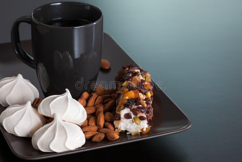 Svarten kuper med marängar, mandelar och marshmallowen royaltyfria bilder
