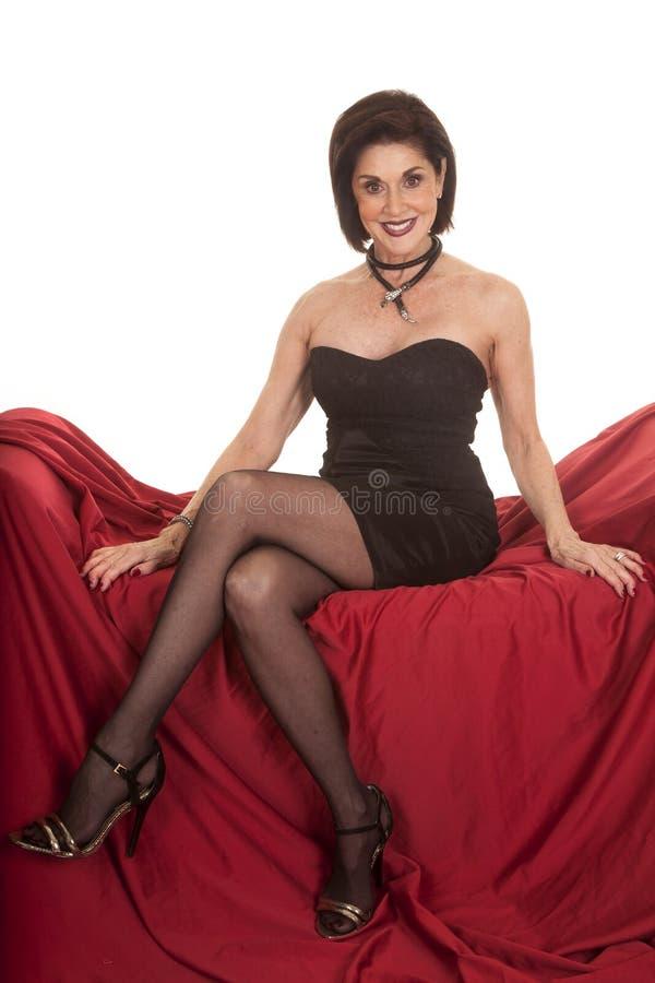 Svartklänningen för äldre kvinna sitter på rött leende royaltyfria bilder