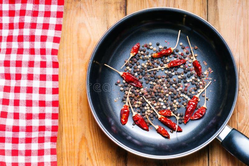 Svartpepparärtor och torkade chilipeppar på en stekpanna royaltyfri fotografi