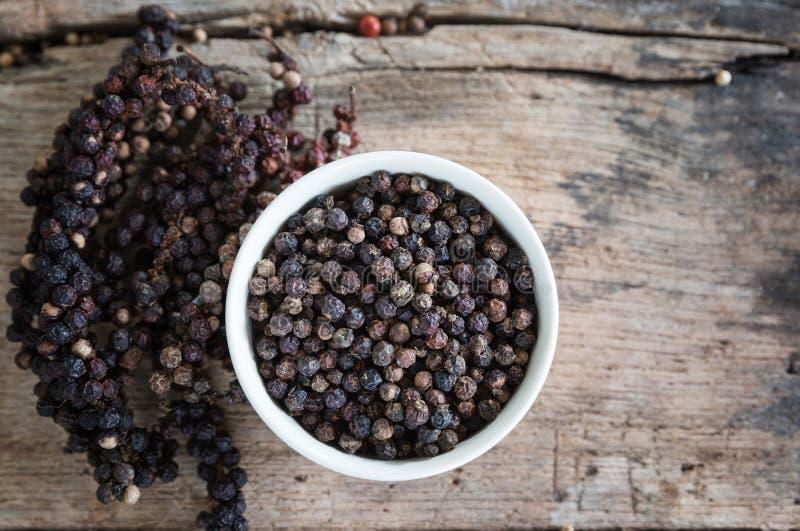 Svartpeppar på den wood tabellen, kryddor för mat royaltyfri fotografi