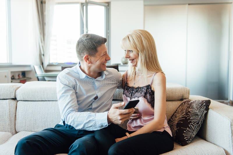 Svartsjuk kvinna som ser hennes partner som pratar på telefonen royaltyfri foto