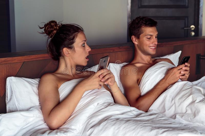 Svartsjuk kvinna som spionerar hennes makemobiltelefon i sovrum royaltyfri bild
