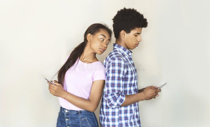 Svartsjuk tonårig flickvän som håller ögonen på hennes pojkvän smsa på telefonen arkivbild