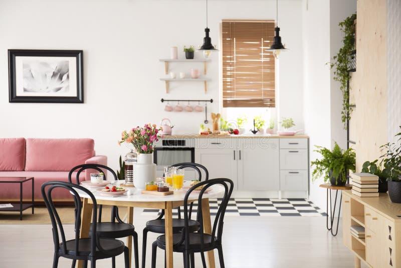 Svartstolar på att äta middag tabellen i öppet utrymmeinre med affischen ovanför rosa färgsoffan och växter Verkligt foto med sud arkivbilder