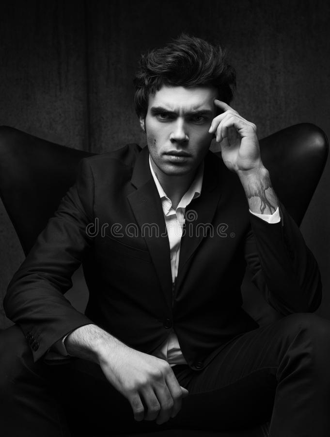 Svartvit affärsstående av ett allvarligt sammanträde för ung man i en stol arkivfoton