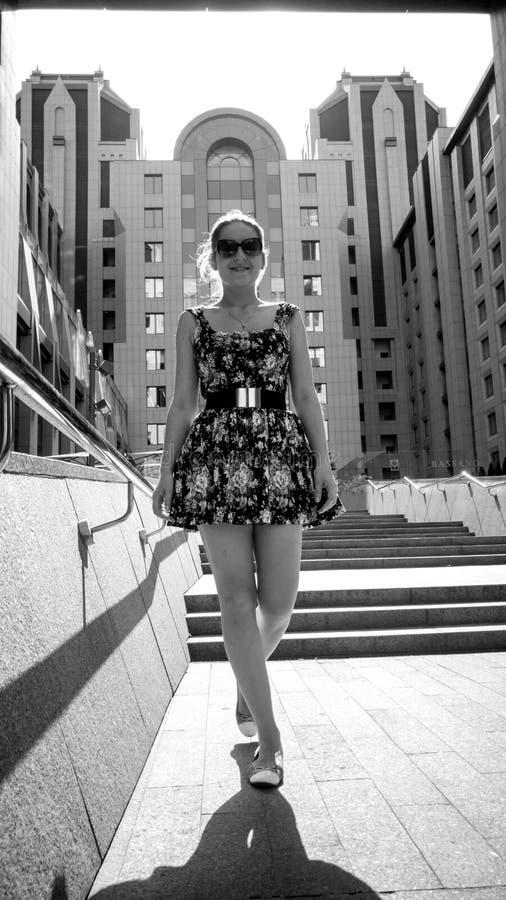 Svartvit bild av att le den unga kvinnan i klänning som går ner stentrappan på gatan på den ljusa soliga dagen royaltyfri bild