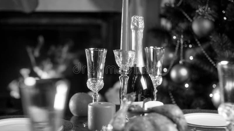 Svartvit bild av Champagneflaskan och exponeringsglas mot den dekorerade julgranen royaltyfri foto