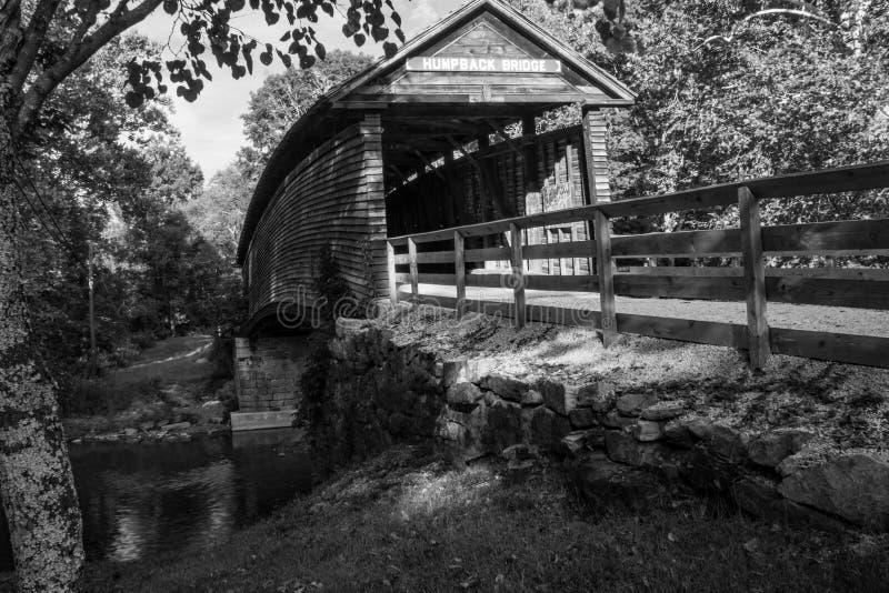 Svartvit bild av den historisk puckelrygg täckte bron arkivfoto