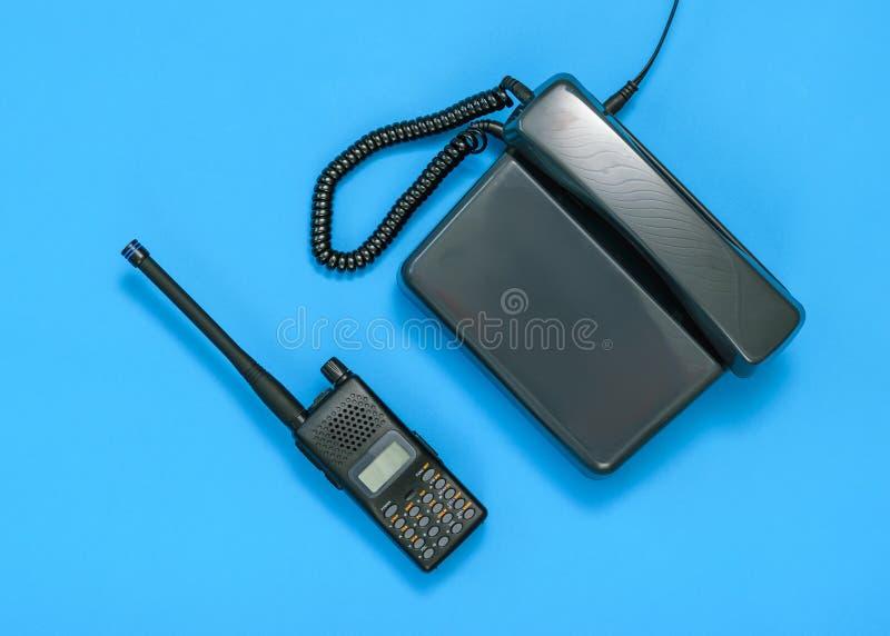 Svartvit bild av en walkie-talkie och en telefon på en blå bakgrund arkivfoton