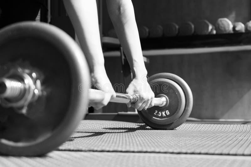Svartvit bild av kvinnahanden som lyfter stålhanteln i en idrottshallmuskelbyggnad arkivfoton