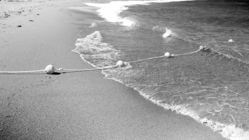 Svartvit bild av linjen för livbesparingboj på repet som ligger på den sandiga havsstranden och flotaing på vattenyttersida royaltyfria foton
