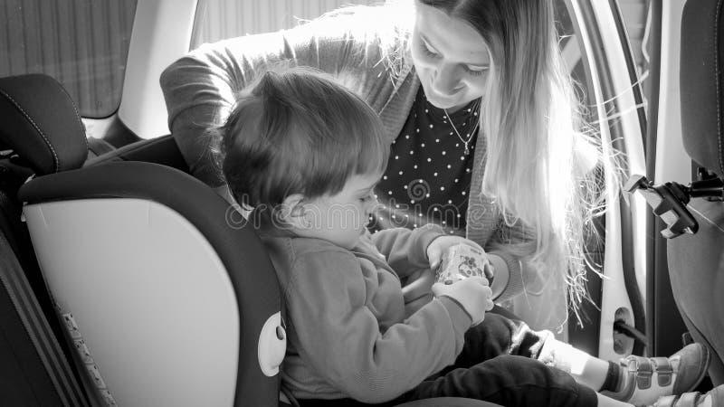 Svartvit bild av säkerhetsbälten för säkerhet för barn för moderfästandebil royaltyfria bilder