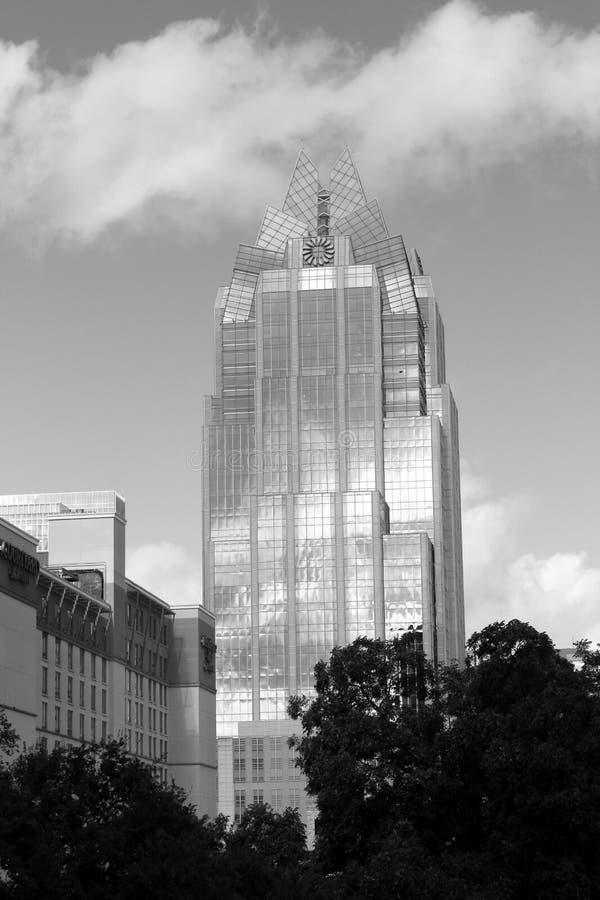 Svartvit bild av uttrycksfulla himlar som reflekterar på yttersida av historisk frostbyggnad, i stadens centrum Austin, Texas, 20 royaltyfri fotografi