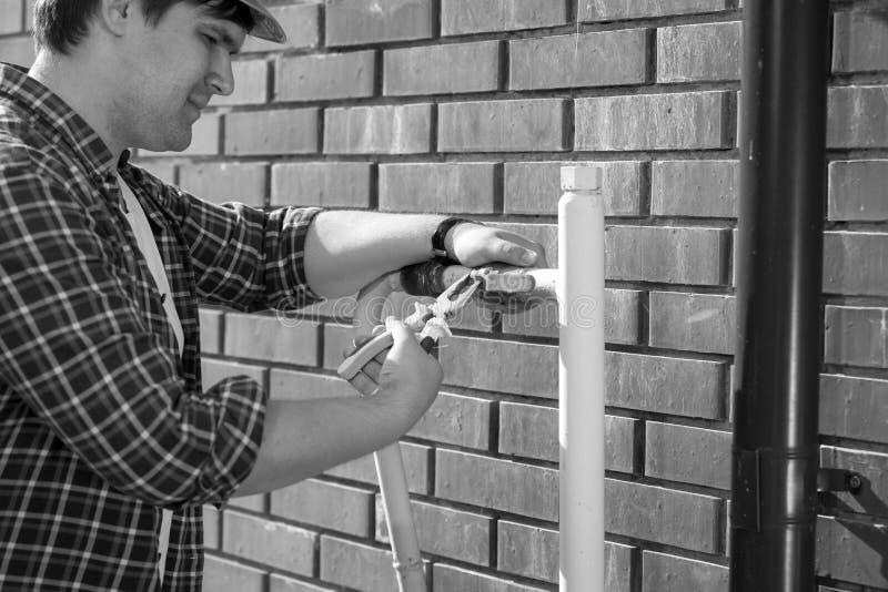 Svartvit bild för Closeup av den manliga arbetaren som reparerar gasventilen med plattång royaltyfri foto