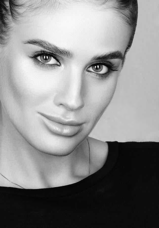 Svartvit closeupskönhetstående av den härliga unga kvinnan med yrkesmässigt färgglat smink fotografering för bildbyråer