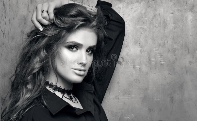 Svartvit closeupstående av den unga härliga kvinnan i den svarta skjortan som framme poserar av en metallvägg arkivbilder