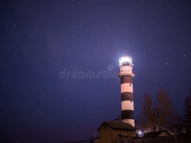 Svartvit fyr på natten i strand för baltiskt hav royaltyfri bild