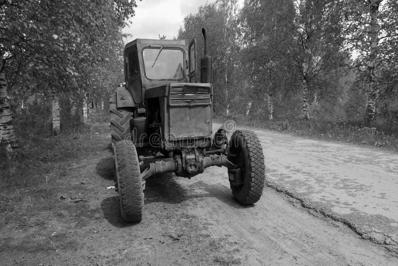 Svartvit lantgårdtraktor som parkeras på sidan av vägen royaltyfria foton