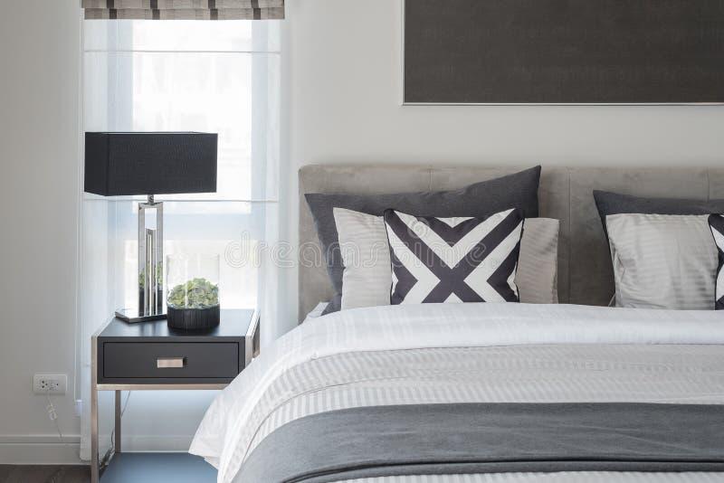 Svartvit modern sovrumstil med den svarta lampan royaltyfri foto