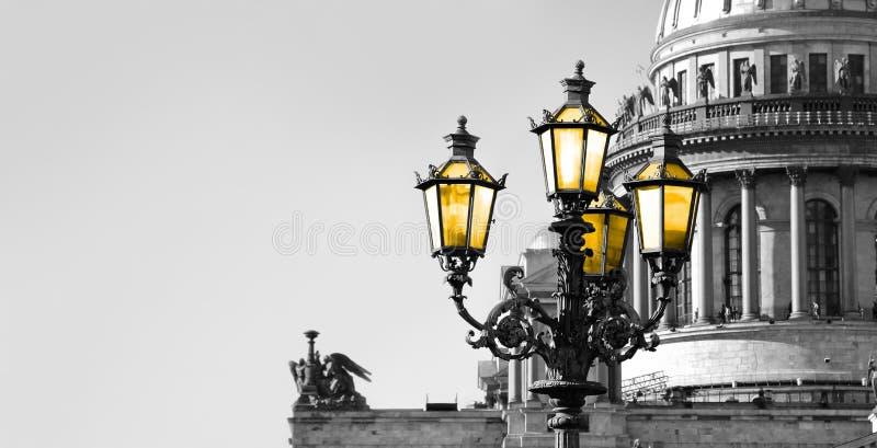 Svartvit sikt av helgonet Isaac Cathedral i St Petersburg med lampan för färgtappninggata med gult ljus fotografering för bildbyråer