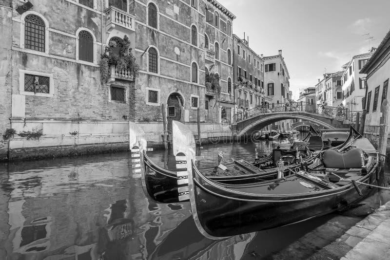 Svartvit sikt av typiska gondoler som parkeras i en Venetian kanal, Venedig, Italien arkivbilder