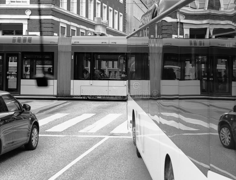 Svartvit sikt på gatatrafik med den overkliga korsningen reflectiom i bussfönster stads- concepnbackgruond royaltyfri bild