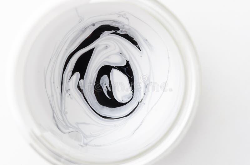 Svartvit sort av målarfärg blandad i exponeringsglaskruset, bästa sikt arkivfoto