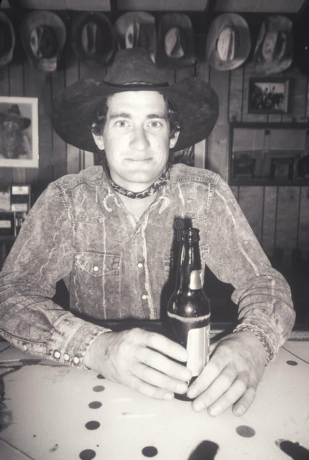 Svartvit stående av cowboyen i stång med öl, Creston, CA royaltyfri bild