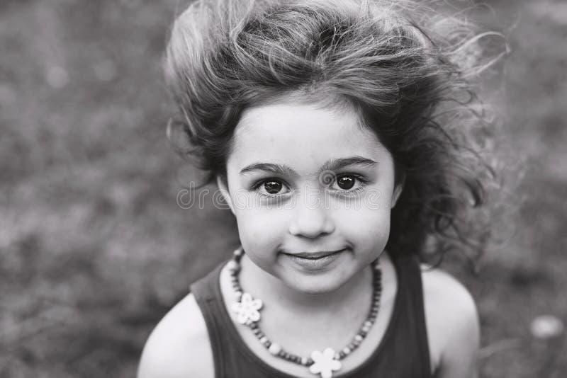 Svartvit stående av den gulliga lilla flickan som utanför ler royaltyfria bilder