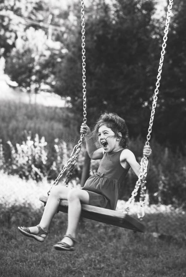 Svartvit stående av den härliga lilla flickan som ler på gunga på sommardagen, lyckligt barndombegrepp blommor fokuserade slappt arkivbild